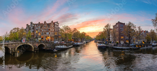 Fotografie, Obraz  Amsterdam Netherlands, sunset panorama city skyline at canal waterfront