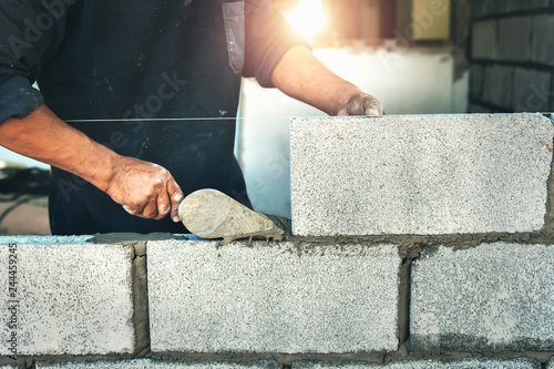 Fotografie, Obraz Worker building wall bricks with cement