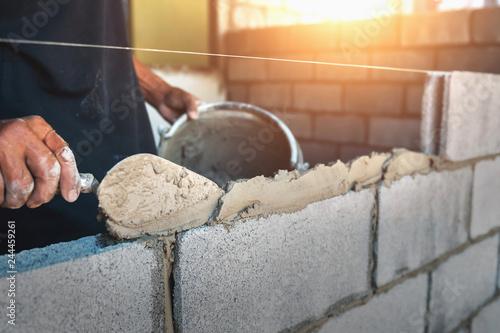Fotografía Worker building wall bricks with cement