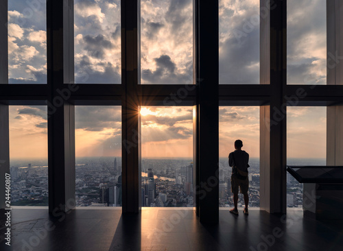 Fényképezés Man standing and sightseeing the bangkok city through windows