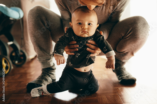 Fotografie, Obraz  Mother squatting on floor with her baby