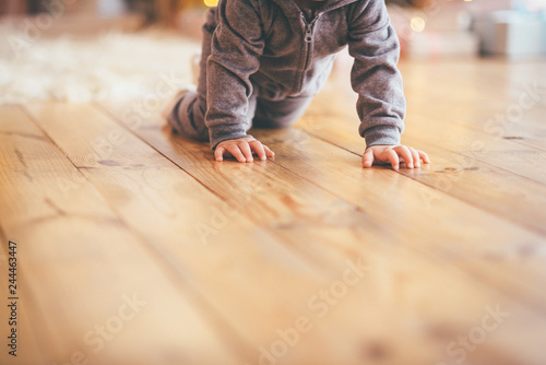 Photo  Baby infant crawls on the wooden floor close up