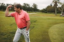 Senior Golfer Celebrating A Hole On Green