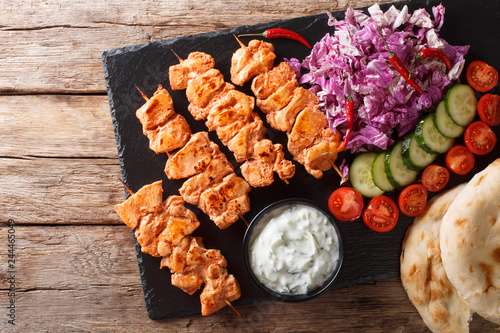 Close-up of chicken skewers with fresh salad, yogurt sauce and pita bread on a slate. horizontal top view