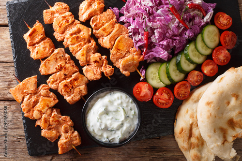 Traditional Taouk chicken kebab with fresh salad, yogurt sauce and pita bread close-up. Horizontal top view
