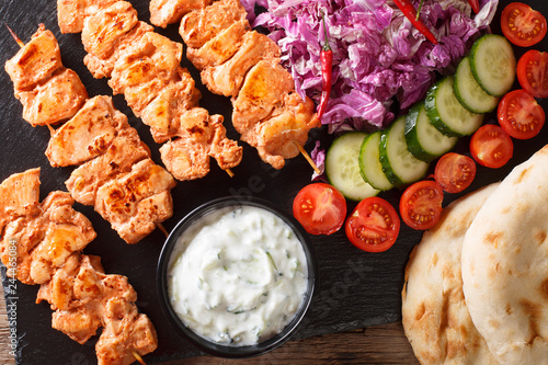 Lebanese Shish Taouk (Tawook)with fresh vegetables, yogurt sauce and pita close-up. horizontal top view