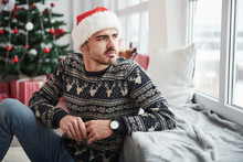 Leaning On The Window Sill. Photo Of Man In Santa Hat And Holiday Clothes Looks Through The Window. Christmas Tree On Background