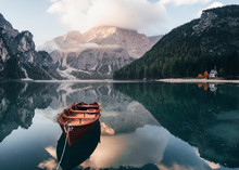 Its Sunlight On The Peak. Wooden Boat On The Crystal Lake With Majestic Mountain Behind. Reflection In The Water. Chapel Is On The Right Coast