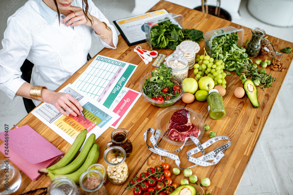 Fototapety, obrazy: Dietitian writing a diet plan, view from above on the table with different healthy products and drawings on the topic of healthy eating