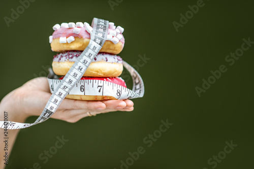 Three sweet donuts covered with measurement tape on the hand on the green background Canvas Print