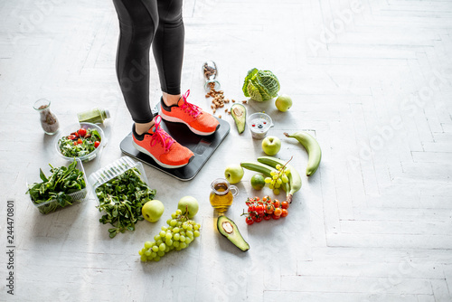 Sports woman weighing on the scales with healthy food around Fototapeta
