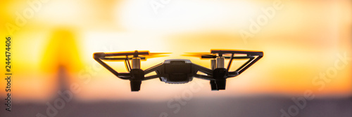 Obraz Drone flying outside in sky sunset banner panorama. Closeup of drone quadcopter with security camera outdoor. - fototapety do salonu