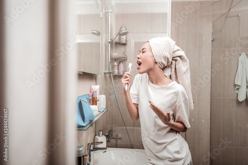 Fotografie, Obraz Delighted positive woman singing in the bathroom
