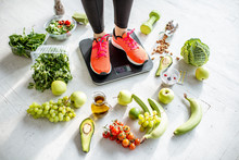 Sports Woman Weighing On The Scales With Healthy Food Around. Weight Loss, Healthy Food And Sports Lifestyle Concept