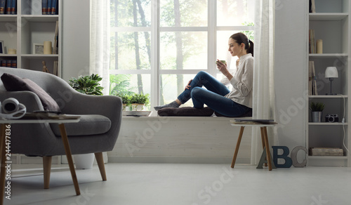Fototapeta Woman relaxing at home and having coffee