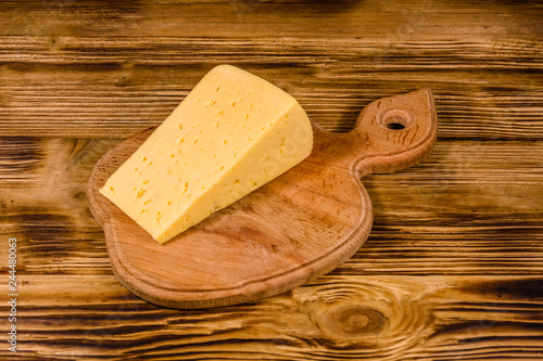 Cutting board with piece of cheese on wooden table