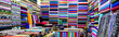 canvas print picture - clothes in shop,Rolls of fabric and textiles for sale stacked on shelves in shop, View of cloth rolls of different colors and patterns on shelves in fabric store