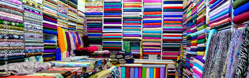 Obraz clothes in shop, Rolls of fabric and textiles for sale stacked on shelves in shop, View of cloth rolls of different colors and patterns on shelves in fabric store - fototapety do salonu