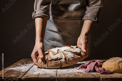 Papel de parede Baker or chef holding fresh made bread