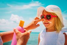 Mother Put Sunblock Cream On Little Daughter Face At Beach