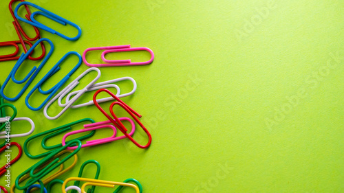 Fotomural  Paper clips on green background with copyspace