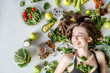 Leinwanddruck Bild - Beauty portrait of a woman surrounded by various healthy food lying on the floor. Healthy eating and sports lifestyle concept