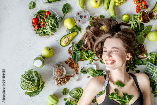 Beauty portrait of a woman surrounded by various healthy food lying on the floor. Healthy eating and sports lifestyle concept