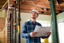 Architect Inside House Being Renovated Studying Plans
