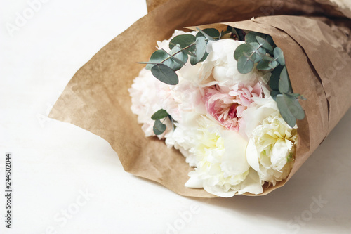 Bouquet of soft pink and white peony flowers and eucalyptus branches wrapped in brown kraft paper on white table background. Feminine style stock photo. Selective focus.