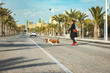 Girl crossing the street with her happy Basset hound on a beautiful beach street stuck with coconut palms and palm trees. Woman walking her dog with sausage in the crosswalk