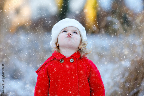 e8117f1ce28 Outdoor winter portrait of little cute toddler girl in red coat and white  fashion hat barret. Healthy happy baby child walking in the park on cold  day with ...