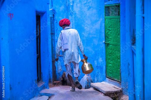 Man wearing traditional clothing walking in blue street, Bundi,India Poster Mural XXL