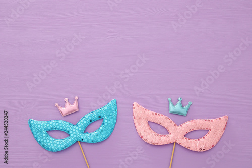 carnival party celebration concept with colorful masks over purple wooden background. Top view. Flat lay.