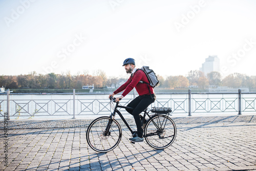 Valokuva  Hipster businessman commuter with electric bicycle traveling to work in city