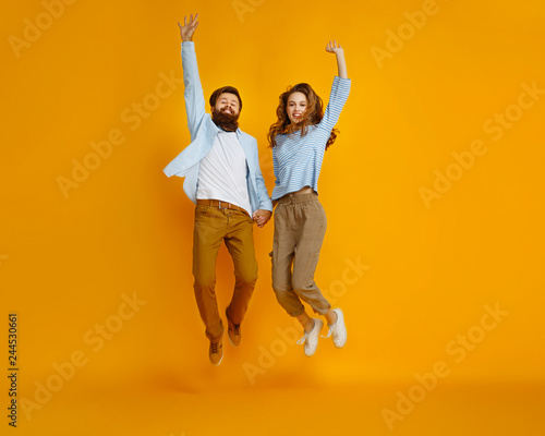 couple of emotional people man and woman jumping on yellow background Fototapeta