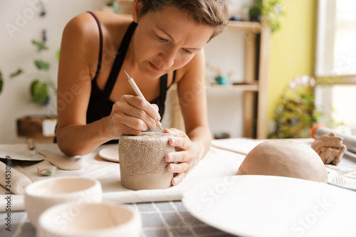 Fotografía  Young woman ceramic and pottery products