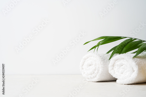 Spa concept: two white fluffy towels twisted into rolls on a light surface with Tapéta, Fotótapéta