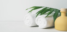 Spa Concept: Beautiful Ceramic Bottle, White Towels And Palm Leaf On Concrete Light Surface With Copy Space.