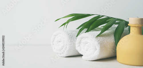 Fotomural Spa concept: beautiful ceramic bottle, white towels and palm leaf on concrete light surface with copy space