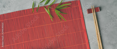 Obraz Bamboo mat and chopsticks on gray stone background for your own design of Asian food concept - fototapety do salonu