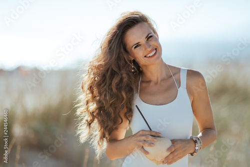 Photo  smiling young woman holding coconut with straw on beach