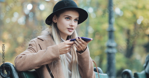 Happy young woman using a smartphone voice recognition function. She Sitting on bench in autumn park and dictates thoughts, voice dialing message