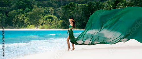 Poster Tissu Beautiful Woman with Flying Fabric of Emerald Color on the Coast of the Ocean. Tropical Island