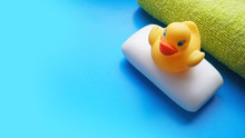 Towel, Soap And Yellow Toy Duck On A Blue Background. Flat Lay Photo, Top View