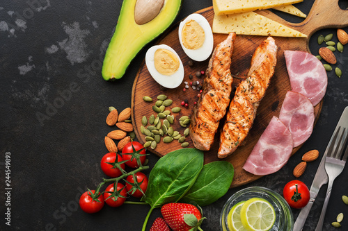Photo Keto lunch or dinner - grilled salmon, vegetables, boiled egg, water with lime, nuts, ham and cheese on a dark background