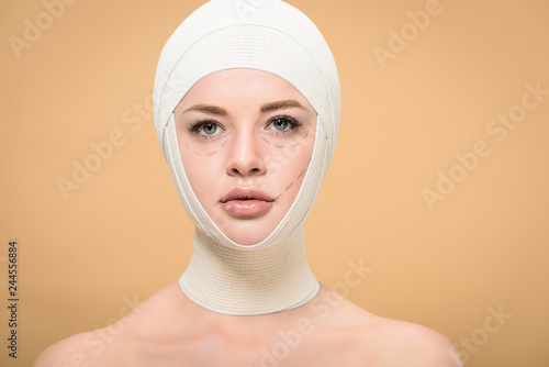 young woman with bandages over head and marks on face looking at camera isolated Canvas Print