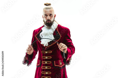 Fényképezés The young man wearing a traditional medieval costume of marquis posing at studio with whip