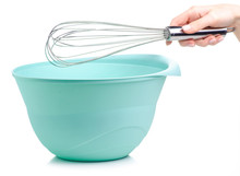 Green Bowl And Kitchen Whisk Corolla In Hand On White Backgrund Isolation
