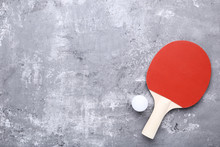 Table Tennis Racket With Ball On Grey Wooden Table