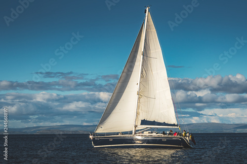 Close-up sailing yacht. Northern Ireland. Outdoor activity. Lone boat on the water surface. Overwhelming marine scene. Irish shoreline on the horizon. Blue cloudy sky background.